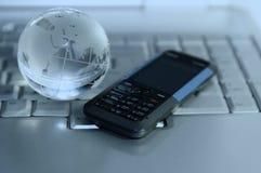 Zellulare und Glaskugel auf Laptoptastatur Lizenzfreies Stockfoto