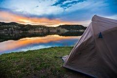 Zelt, das Lakeshore durch bei Sonnenuntergang oder Sonnenaufgang im Mounta kampiert Lizenzfreie Stockbilder