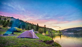 Zelt, das Lakeshore durch bei Sonnenuntergang oder Sonnenaufgang im Mounta kampiert Lizenzfreie Stockfotografie