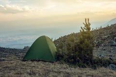 Zelt mit Touristen auf dem Hintergrund der Frühlingslandschaftsansicht der Berge und des Himmels bei Sonnenuntergang Lizenzfreies Stockbild