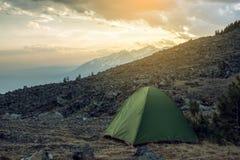 Zelt mit Touristen auf dem Hintergrund der Frühlingslandschaftsansicht der Berge und des Himmels bei Sonnenuntergang Stockbilder