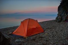 Zelt nahe Seeufer bei dem schönen Sonnenuntergang lizenzfreie stockbilder
