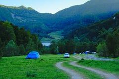 Zelte und Autos von Campern in den rumänischen Bergen morgens stockbilder