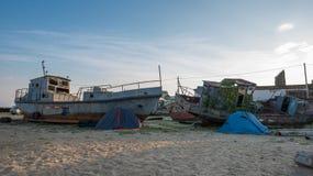 Zelte und Schiffe auf dem Ufer Stockbilder