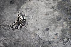 Zementieren Sie Boden mit einem Loch von Zigarettenkippen Stockbilder