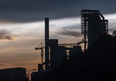 Zementieren Sie Fabrik in der Abend-Dämmerung mit dunklem Wolkenhimmel Lizenzfreie Stockfotos