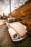 Zemun, Serbia - 17 febbraio 2019 - vecchia ha arrugginito Volkswagen Beetle bianco parcheggiato accanto al muro di mattoni aranci fotografie stock