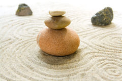 Zen. Closeup of a small serene zen sand and stone garden. One stone pile is located in focus while two stones are in the background Royalty Free Stock Photography