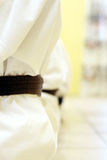 Zen. Close up of people lining up during karate practise, focus on the first belt stock photo