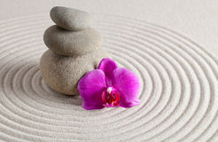 Zen Background. A Stack of stones and a orchid on raked sand - a niche zen-like backgorund Royalty Free Stock Image
