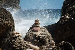 Zen balanced rocks with backdrop of water splash. Zen balanced Rocks with backdrop of ocean water splashing from waves Stock Photos