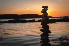 Zen balanced stones stacked on sea coast at sunset. Balance and equilibrium concept.  stock photo