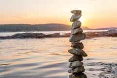 Zen balanced stones stacked on sea coast at sunset. Balance and equilibrium concept.  stock photos