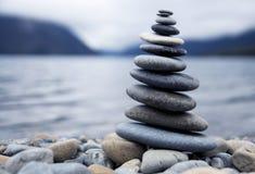 Zen Balancing Pebbles Next a Misty Lake fotos de archivo