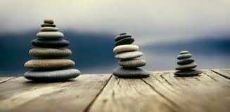 Zen Balancing Pebbles Next a Misty Lake Concept imagen de archivo libre de regalías