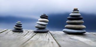 Zen Balancing Pebbles Next zu Misty Lake Lizenzfreie Stockfotografie