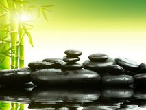 Zen basalt stones with green bamboo on water. Spa and Wellness concept. Zen basalt stones with green bamboo on water. Spa and Wellness concept stock photos