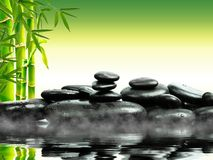 Zen basalt stones with green bamboo on water. Spa and Wellness concept. Zen basalt stones with green bamboo on water. Spa and Wellness concept stock photography
