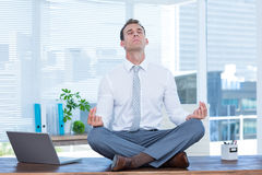 Zen businessman doing yoga meditation stock image