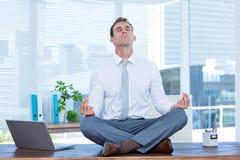 Zen businessman doing yoga meditation Stock Image