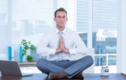 Zen businessman doing yoga meditation Stock Photos