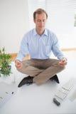 Zen businessman meditating on his desk Stock Photo