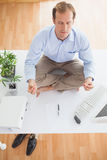 Zen businessman meditating on his desk Stock Photography