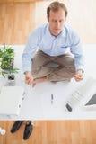 Zen businessman meditating on his desk Stock Photography