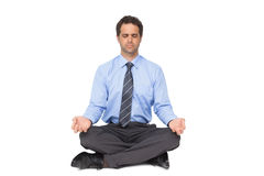 Zen businessman meditating in lotus pose with eyes closed Royalty Free Stock Photography