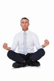 Zen businessman meditating in lotus pose Stock Photo