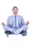 Zen businessman meditating in yoga pose Stock Image