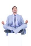 Zen businessman meditating in yoga pose Stock Image