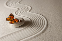 Zen butterfly. Sand background with rock and butterfly Royalty Free Stock Images