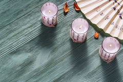 Zen candle and fan with hieroglyphs on a  wooden background Royalty Free Stock Photo