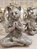 Zen Kitty Cat in Buddha Meditation Pose. Figure of a zen kitty cat in buddha meditation pose with another cat in the background royalty free stock images