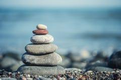Zen-como pedras na praia sob o sol Imagens de Stock