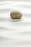Zen concept. Stone on waves in the sand - focus or zen concept royalty free stock photo