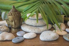 Zen concept: buddha, stones pyramid, palm leaf and bamboo. Buddha, stones pyramid, palm leaf and bamboo on wooden background stock photography