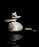 Zen Corporate. Pile of pebble Stones and White Feather over Black Background stock image