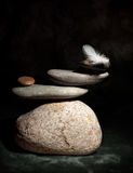 Zen Corporate. Pile of pebble Stones and White Feather over Black Background royalty free stock image