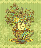 Zen-doodle cup of tea with flowers yellow green  blue on green background Stock Photo