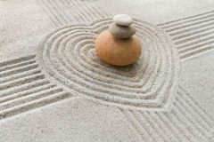 Zen garden. A close view on a small Zen garden. Stones on a stack are located in the center of a heart in gray sand Stock Photos