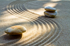 Zen garden. Close up of a zen rock garden with a pile of stones in sand Stock Image