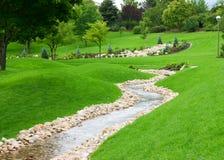 Zen garden. Stream of water flowing through grassy hills with trees Stock Photo