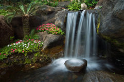 Zen Garden. Colorful flowers and palm trees surround a peaceful waterfall within a Japanese garden Stock Images