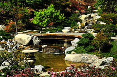 Zen Garden. Bamboo bridge over a stream in a beautiful flower filled Japanese Zen garden Royalty Free Stock Images