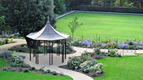 Zen garden gazebo pergola. Photo of beautiful garden grounds with bandstand style pergola as main attraction centrepiece Stock Photos