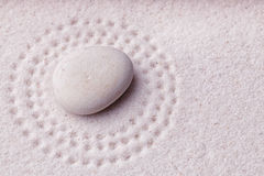 Zen garden with a relaxing beige stone with small dots Royalty Free Stock Images