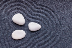 Zen garden with a silk white stones with wave patterns in sand Royalty Free Stock Photos
