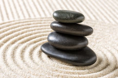 Zen garden with stacked black pebbles Royalty Free Stock Photos